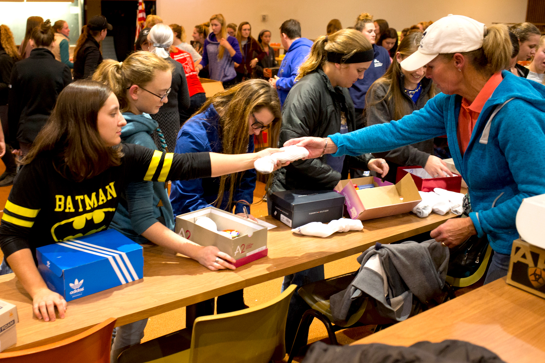 Carla Wennberg hands a student some socks for the packages. Photo by Rooney Coffman
